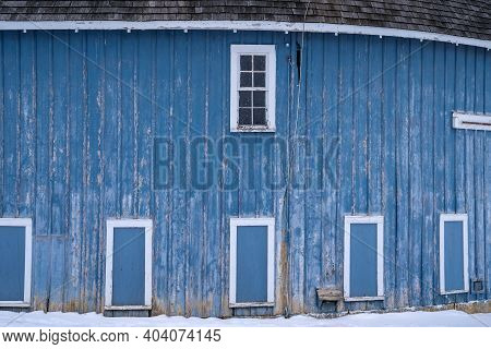 Blue Doors And Windows On The Side Of A Rustic Round Barn