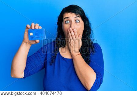 Plus size brunette woman holding credit card covering mouth with hand, shocked and afraid for mistake. surprised expression