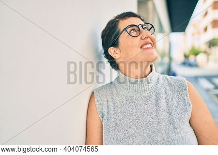 Young plus size woman smiling happy leaning on the wall at the city.