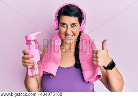 Plus size brunette woman wearing sportswear holding water bottle smiling happy and positive, thumb up doing excellent and approval sign