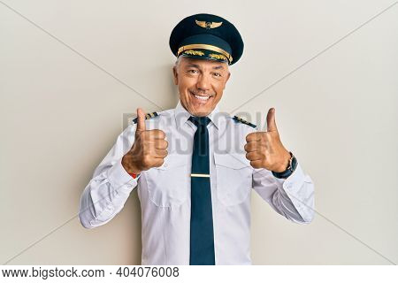 Handsome middle age mature man wearing airplane pilot uniform success sign doing positive gesture with hand, thumbs up smiling and happy. cheerful expression and winner gesture.