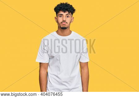 Young arab man wearing casual white t shirt puffing cheeks with funny face. mouth inflated with air, crazy expression.