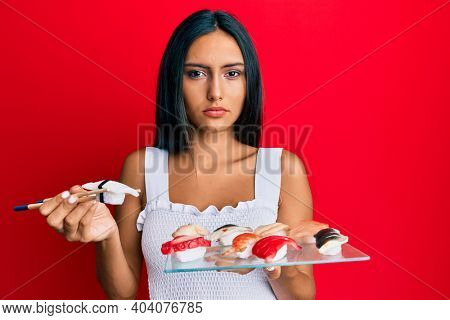 Young brunette woman eating butterfish sushi using chopsticks relaxed with serious expression on face. simple and natural looking at the camera.