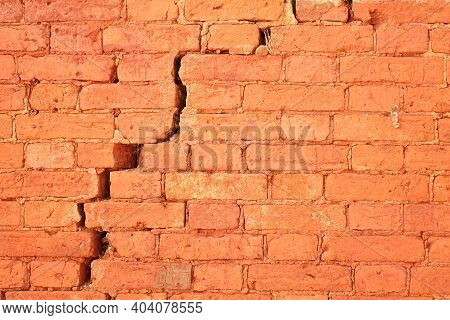 Cracked Red Brick Wall With Big Crack Structure. Damaged Brickwork Surface Texture. Destroyed And Ag