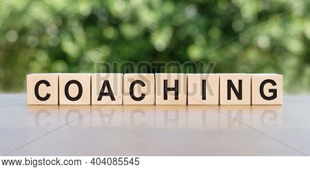 Coaching. Word Written On Wooden Blocks. The Text Is Written In Black Letters And Is Reflected In Th