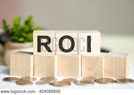 Concept Word Roi On Wooden Blocks On Beautiful Background From Dollar Bills. The Word Roi On Wood Cu