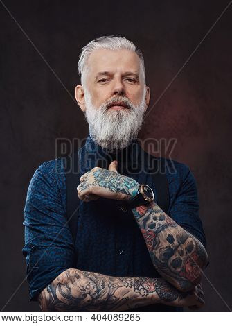 Bearded And Tattooed Old Man With Gray Hairs In Stylish Clothing Poses In Dark Background.