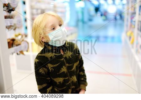 Boy In Facemask Examines Goods On Showcase Of Store Or Pharmacy In Shopping Mall, In Airport Or At G