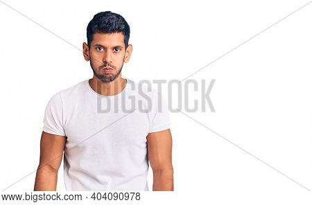 Young latin man wearing casual clothes puffing cheeks with funny face. mouth inflated with air, crazy expression.