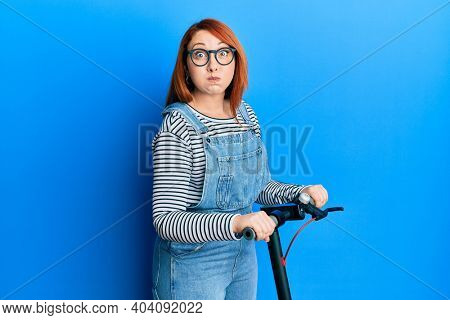 Beautiful redhead woman standing on modern scooter over blue background puffing cheeks with funny face. mouth inflated with air, catching air.
