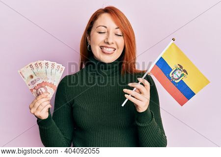 Beautiful redhead woman holding colombia flag and 10 colombian pesos banknotes sticking tongue out happy with funny expression.