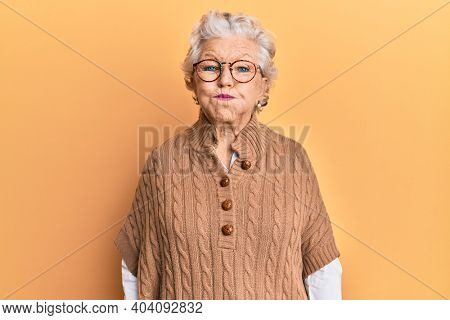 Senior grey-haired woman wearing casual clothes and glasses puffing cheeks with funny face. mouth inflated with air, crazy expression.