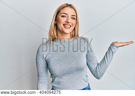 Young caucasian woman wearing casual clothes smiling cheerful presenting and pointing with palm of hand looking at the camera.