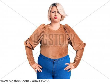 Young blonde plus size woman wearing casual sweater puffing cheeks with funny face. mouth inflated with air, crazy expression.