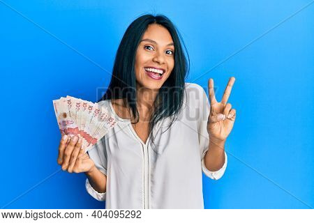 Young african american woman holding 10 colombian pesos banknotes smiling looking to the camera showing fingers doing victory sign. number two.