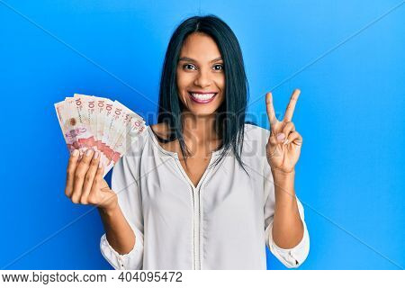 Young african american woman holding 10 colombian pesos banknotes smiling with happy face winking at the camera doing victory sign with fingers. number two.