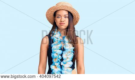 Young beautiful latin girl wearing hawaiian lei and summer hat puffing cheeks with funny face. mouth inflated with air, crazy expression.