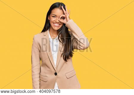Beautiful hispanic woman wearing business jacket doing ok gesture with hand smiling, eye looking through fingers with happy face.