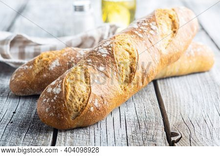 Two crispy fresh baguettes on a wooden table.