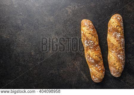 Crispy fresh baguettes on black table. Top view.
