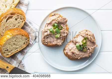 Liver pate on sliced baguette on plate. Top view.