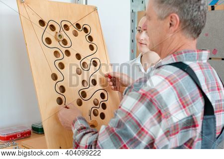 Man with therapist in occupational therapy testing his dexterity on a game board