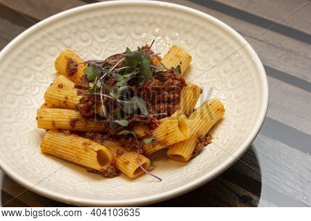 Rigatoni Pasta With Sugo Sauce And Lamb Ragout, With Coriander Leaves On Top.