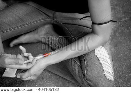 Black And White Image Of Hard Drugs With Hand Holding  Injecting Heroin Into A Vein. Narcotic Recrea