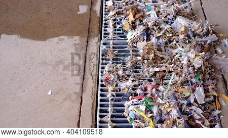 Small Pieces Of Debris Are Stacked On The Grate Over The Drain