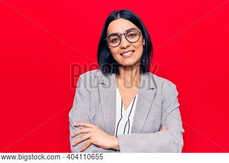 Young beautiful latin woman wearing business clothes happy face smiling with crossed arms looking at the camera. positive person.