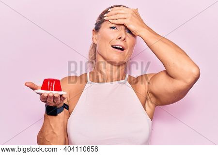 Middle age caucasian blonde woman holding sweet strawberry jelly stressed and frustrated with hand on head, surprised and angry face