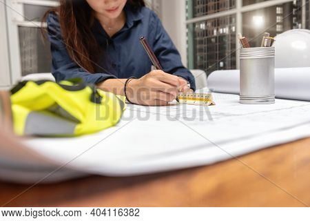 Engineer Woman Designer Sketching With Blueprint Architecture On Desk Office In-home At Night, Worki