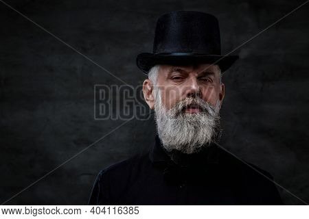 Dressed In Old Fashioned Style Clothing Grandfather With Top Hat And Gray Hairs Poses In Dark Backgr