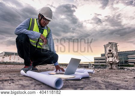 Civil Engineer Wearing High Visibility Safety Vest And Helmet Squatting To Looking Laptop With Drawi