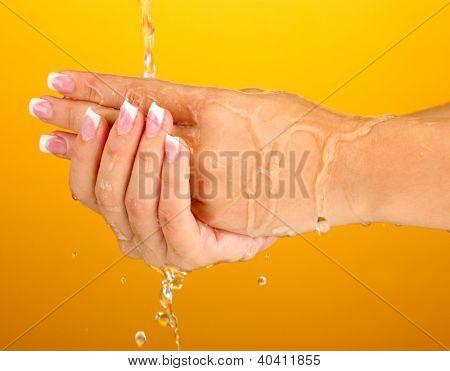 Washing woman's hands on orange background close-up