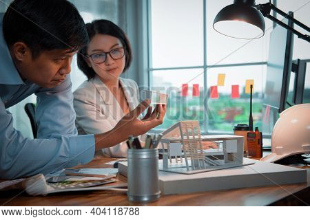 Asian Architect-designer Holding The Part Of The Model Of Modern Box House While Discussing With Tea