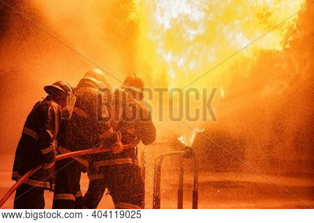 Firefighter Using Extinguisher Or Twirl Water Fog Type Fire Extinguisher To Spray Water From Hose Fo