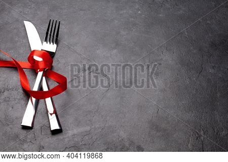 Valentines day table with silverware and red ribbon. Top view with copy space