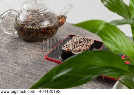 Teapot Glass Teapot With Herbal Tea And Rolls With Eel And Sesame Seeds On Gray Granite Stone
