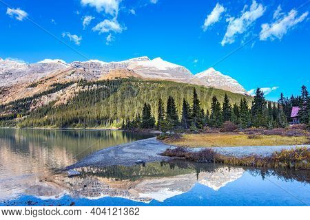 Canada. Rocky Mountains. Sun and mountains are reflected in the smooth water of the lake. Glacial lake Bow with clear azure water. Sunny autumn day