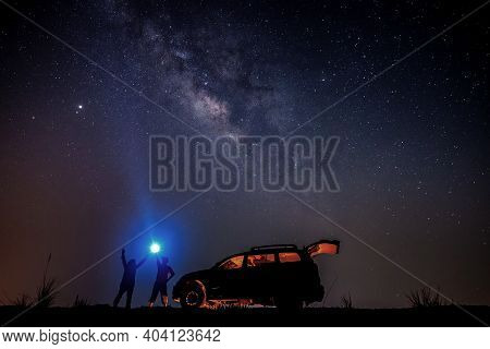 Man Tourist With Flashlight Near His Camp Car At Night. Space Background With Noise And Grain. Night