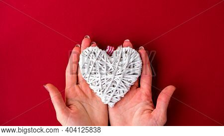 Female Hands Hold Heart On Red Background. Valentines Day. Holiday Background With Copy Space. Card