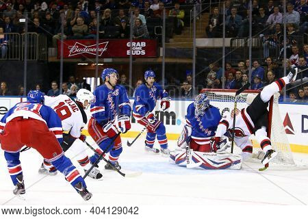 NEW YORK-APR 27: New Jersey Devils center Travis Zajac (19) takes a shot on New York Rangers goalie Henrik Lundqvist (30) with New Jersey Devils left wing Patrik Elias (26) at Madison Square Garden.