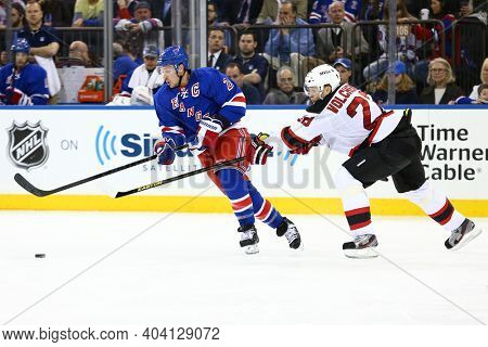 NEW YORK-APR 27: New York Rangers right wing Ryan Callahan (24) and New Jersey Devils defenseman Anton Volchenkov (28) battle for the puck at Madison Square Garden on April 27, 2013 in New York City.