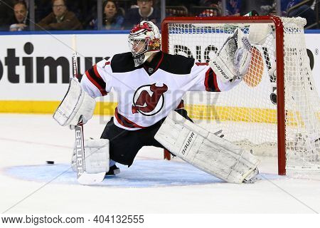 NEW YORK-APR 27: New Jersey Devils goalie Johan Hedberg (1) deflects the puck against the New York Rangers at Madison Square Garden on April 27, 2013 in New York City.