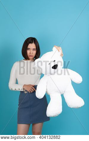 Disappointed With A Cheap Gift, An Asian Woman Holds A Large White Teddy Bear By The Ear , Isolated