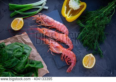 Large Langoustines Shrimp On A Black Stone On The Black Kitchen Table. Seafood For A Healthy Diet. I