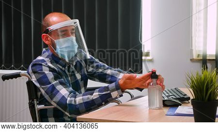 Disabled Entrepreneur Sitting In Wheelchair With Protection Mask Cleaning Hands Before Typing On Com