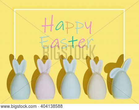 Happy Easter Greeting Card Wit Rabbits On Yellow Background. Flat Lay Composition With Easter Eggs A