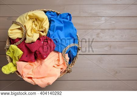 Wicker Laundry Basket With Different Clothes On Wooden Background, Top View. Space For Text